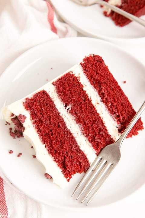 Slice of classic red velvet cake on a plate.