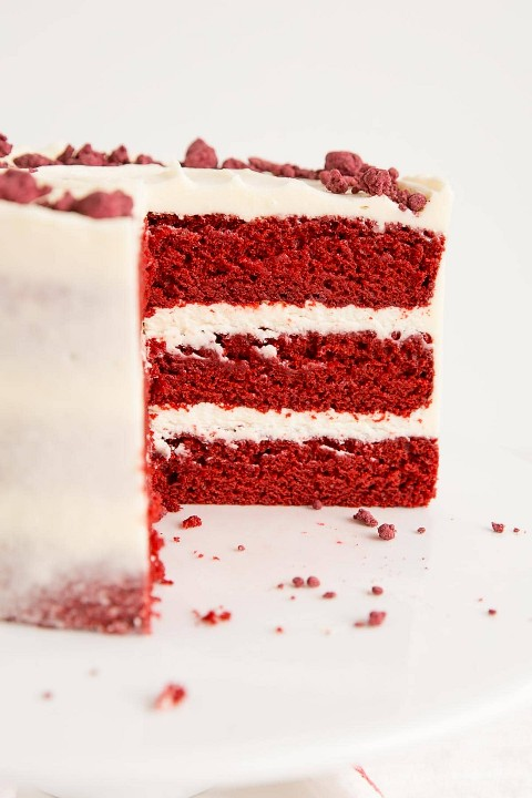 Cross section of a three layer red velvet cake with cream cheese frosting.