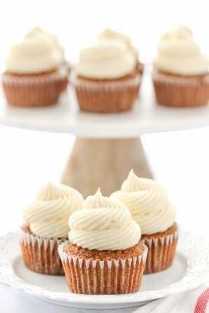 Un plato blanco decorativo con tres pastelitos de pastel de zanahoria cubiertos con queso crema y un pastel de mármol.