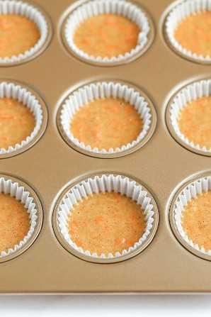 Una bandeja para muffins rellena con forros para cupcakes y pastel de pastel de zanahoria.