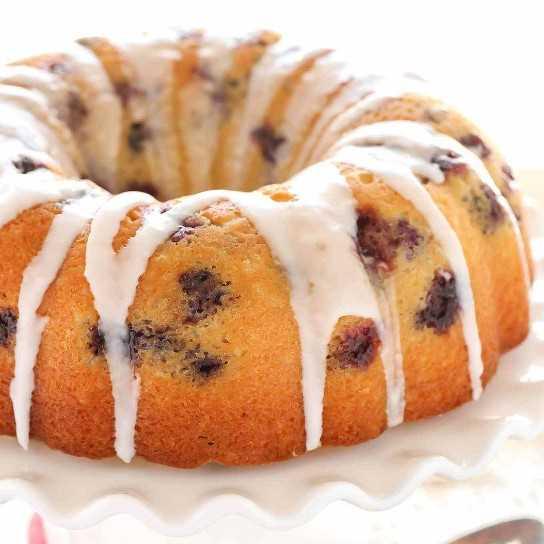 Un pastel de limón húmedo lleno de arándanos frescos y cubierto con un glaseado de limón dulce. ¡Este pastel de limón y arándano azul es un postre perfecto para los amantes del limón!