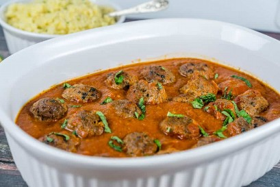Un plato de cazuela con albóndigas marroquíes en una sabrosa salsa de tomate con especias | Babaganosh.org