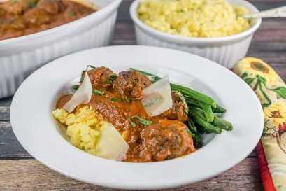 Plato de cena de albóndigas marroquíes con polenta y judías verdes con platos de cazuela en el fondo | Babaganosh.org