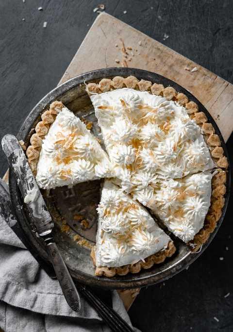 Tarta de crema entera de coco en un plato de pastel con corte de rodajas. Pie está sentado en una tabla de cortar de madera sobre una superficie oscura.
