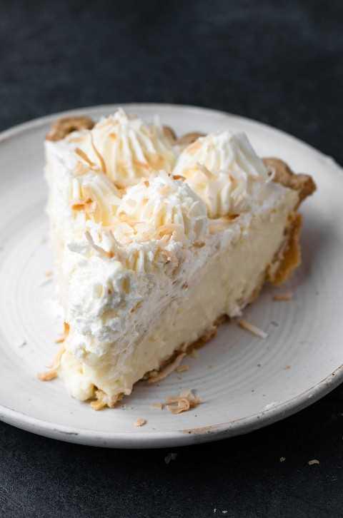 Una sola rebanada de pastel de crema de coco hecho desde cero en un plato de postre blanco.