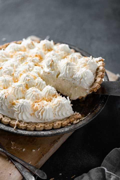 Retirar una rebanada de pastel de crema de coco de todo el pastel de crema de coco en el plato de pastel.