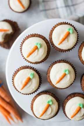 Vista desde arriba de pastelitos de pastel de zanahoria cubiertos con glaseado de queso crema entubado para que parezca una zanahoria.