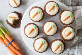 Vista desde arriba de cupcakes de pastel de zanahoria en un soporte para pasteles, con un manojo de zanahorias frescas y un paño a cuadros debajo.
