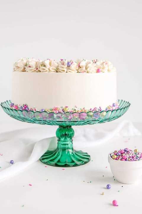 El tiro del perfil de la torta blanca con el buttercream blanco y asperja.