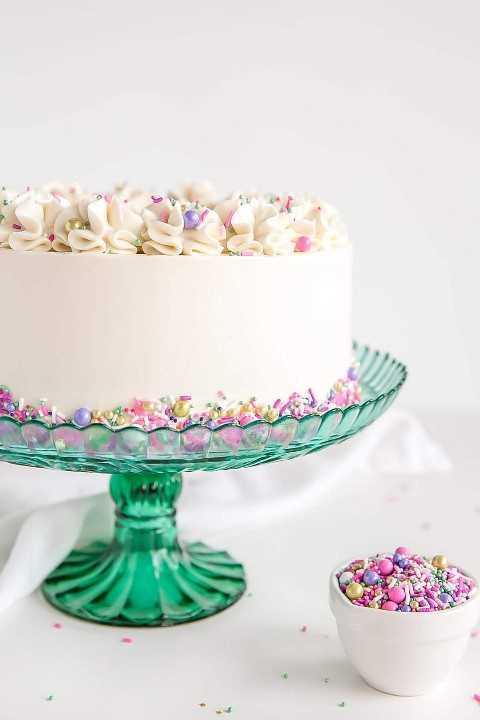 Tiro lateral de una torta blanca en un soporte verde de la torta.