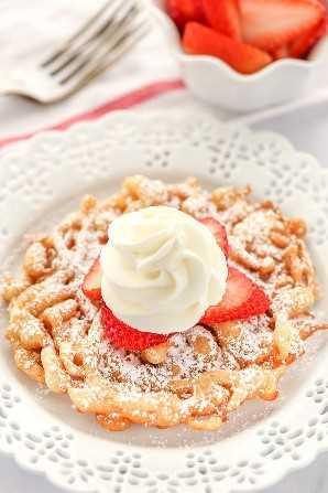 Un pastel de embudo casero cubierto con fresas y crema batida casera sentado en un plato blanco decorativo.