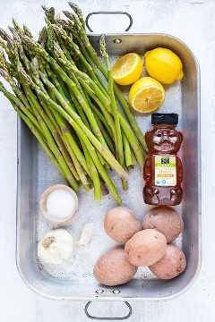 Espárragos, limones frescos, miel, papas rojas, ajo y sal como ingredientes de una receta de pollo al horno con ajo y limón.