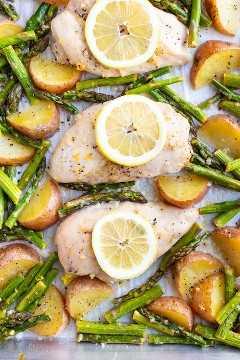 Receta saludable de pollo con ajo y limón con espárragos y papas rojas que se ha cocido en el horno.