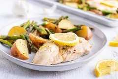 Un plato blanco lleno de pollo de limón saludable con patatas asadas y espárragos.