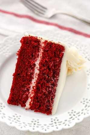 Una sola rebanada de pastel de terciopelo rojo en un plato blanco decorativo con una servilleta blanca y un tenedor en el fondo.