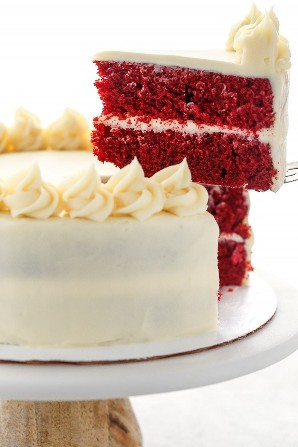 Una rebanada de pastel de terciopelo rojo que se retira del pastel completo en un soporte de pastel de mármol.
