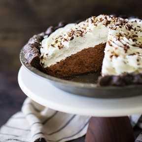Tarta de crema de chocolate con costra de chocolate, crema batida y virutas de chocolate. Se saca una rebanada del pastel para que se vea el relleno de mousse de chocolate esponjoso.