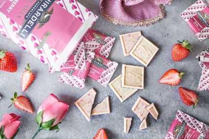 Los cuadrados de fresa Ghirardelli se derraman de una bolsa, con algunos caramelos sin envolver y rotos, con fresas frescas y capullos de rosa rosados.