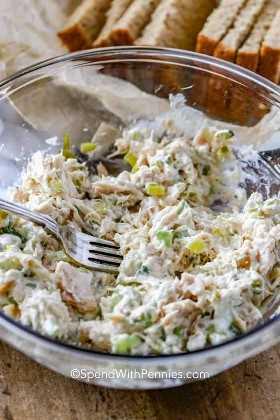 Un claro tazón lleno de ensalada de atún con pan fresco en el fondo.