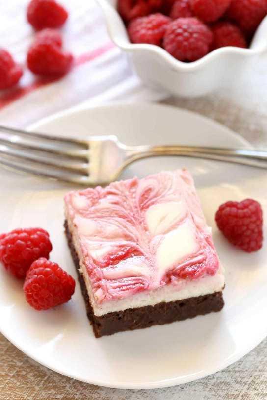 Una base de brownie dulce rematada con una capa de tarta de queso suave y cremosa y un remolino de frambuesa. ¡Estos brownies de tarta de frambuesa son un hermoso postre para cualquier ocasión!