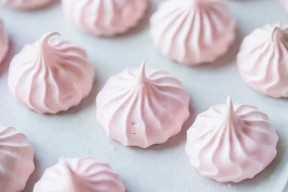 Besos de merengue al horno de color rosa claro en una bandeja para hornear forrada de pergamino.
