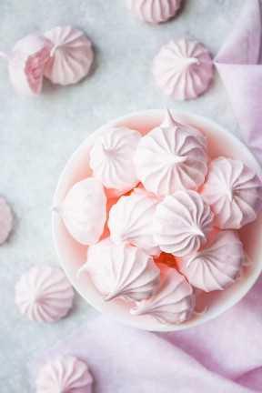 Imagen de arriba de las galletas del merengue del color de rosa de bebé en un tazón de fuente blanco con un paño rosado.