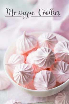 """Cuenco lleno de besos de merengue rosa pastel sobre un fondo blanco con superposición de texto que dice """"Galletas de merengue""""."""