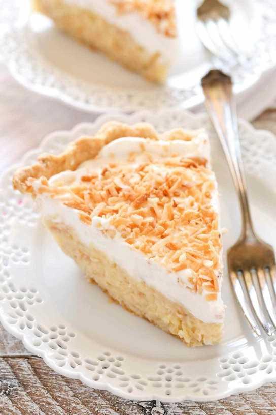 Una masa de tarta casera rellena con un relleno de coco cremoso y cubierta con crema batida fresca y coco tostado. ¡Esta receta casera de crema de coco es tan fácil de hacer y deliciosa!