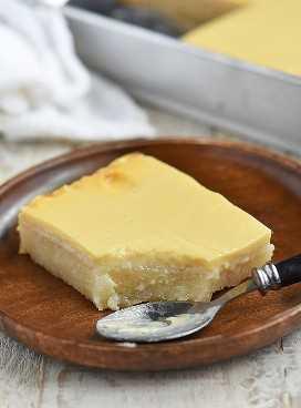 Rebanada de pastel de yuca en un plato de madera con una cuchara