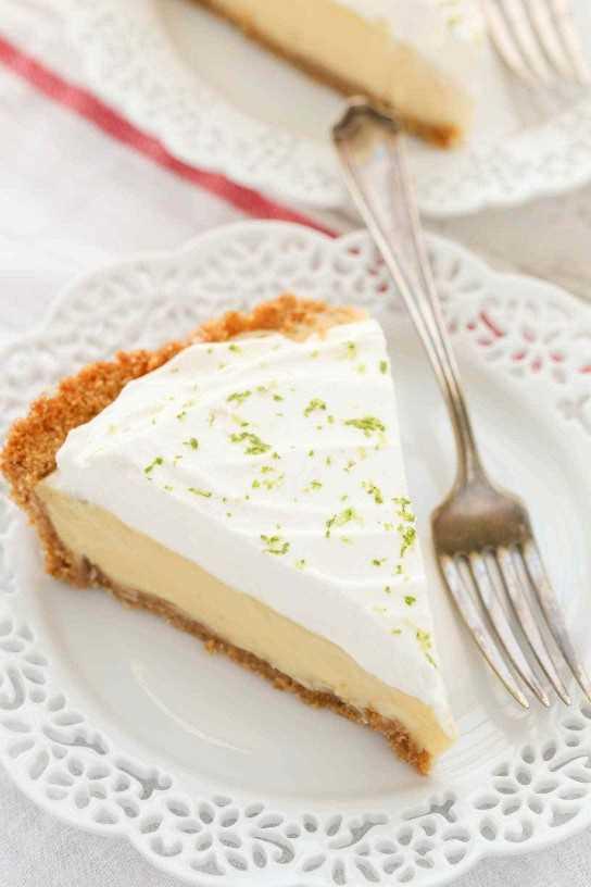 Este clásico Key Lime Pie presenta una costra de galleta de graham casera fácil, un relleno de pastel de lima suave y cremoso y crema batida casera en la parte superior. ¡El postre perfecto para los amantes de la lima!