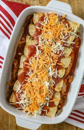 Un plato de cazuela lleno de enchiladas de carne molida con salsa de enchilada y queso.