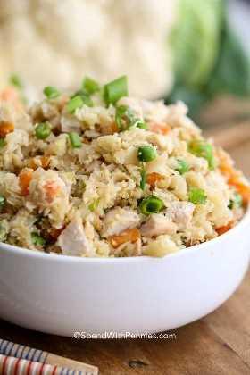 Coliflor de arroz frito sazonado con jengibre y ajo con pollo y verduras en un tazón