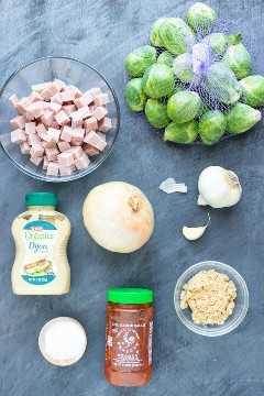 Restos de jamón en cubos, una libra de coles de Bruselas, cebolla, ajo, mostaza Dijon, pasta de ajo con chile y azúcar moreno como ingredientes de una receta de coles de Bruselas salteadas.