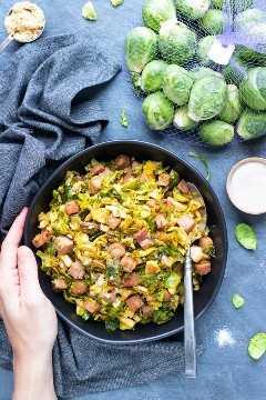 Una bolsa llena de coles de Bruselas junto a un plato de servir lleno de coles de Bruselas salteadas y trituradas con jamón en cubos.