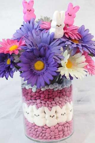 Esta adorable pieza central de Pascua será la decoración de Pascua favorita de todos, tan divertida y fácil de hacer. Todo lo que necesitas son M & M's, Peeps y algunas flores.