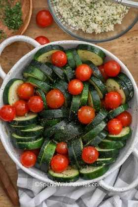 Rebanadas frescas del calabacín en un plato de la cazuela con los tomates