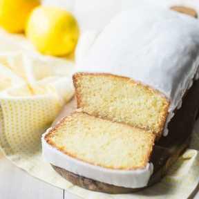 Pan helado del limón en una tabla de cortar de madera con los limones en el fondo.