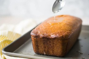 Lloviznando el jarabe de limón sobre el pastel de pan.