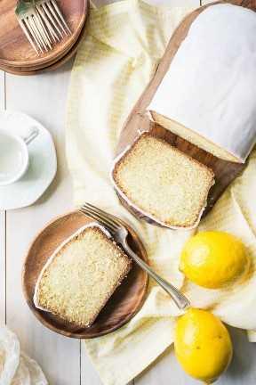 Vista de arriba abajo de la torta helada del pan del limón en una tabla de cortar, con una rebanada de torta en una placa y una servilleta impresa amarilla.