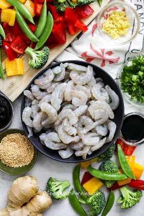 Ingredientes salteados de camarones como camarones crudos, verduras, jengibre y ajo.