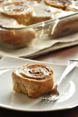 Rollos de canela deliciosos durante la noche en un plato y en una bandeja para hornear