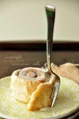 Usando un tenedor para tomar un bocado de uno de nuestros Rollos de canela de trigo con miel durante la noche