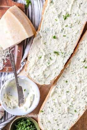 En el lateral hay dos mitades de pan cubiertas con mantequilla de ajo batida, un tazón de mantequilla de ajo vacío, queso parmesano rallado y perejil fresco picado.