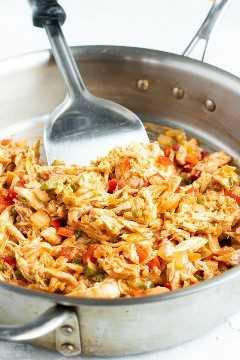 Pollo rallado y salsa en una sartén como relleno para una receta de taquitos al horno.