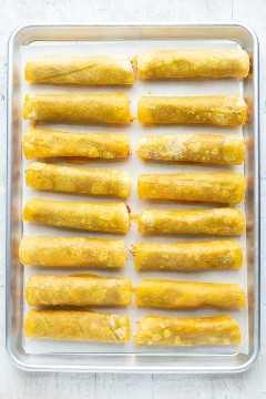 Dieciséis taquitos se enrollaron y colocaron la costura hacia abajo en una bandeja para hornear forrada con papel de pergamino.