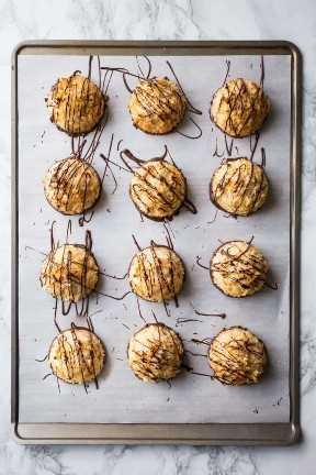 Imagen de arriba de macarrones de coco sumergidos en chocolate negro en una bandeja para hornear forrada de pergamino.
