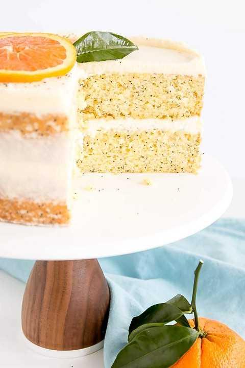 Dos capas de pastel de semillas de amapola anaranjadas cubiertas de un delicioso glaseado de mascarpone.