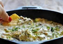 Usando un chip de tortilla para tomar un bocado de nuestro Creamy Brussels Sprout & Shallot Dip