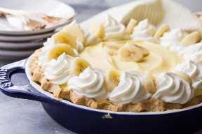 Tarta de crema de plátano con relleno de crema diplomática esponjosa, plátanos reales y crema batida dulce, enclavada en una corteza de pastel casera escamosa.