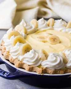 Tarta de crema de plátano con crema esponjosa, remolinos de crema batida y plátanos frescos.